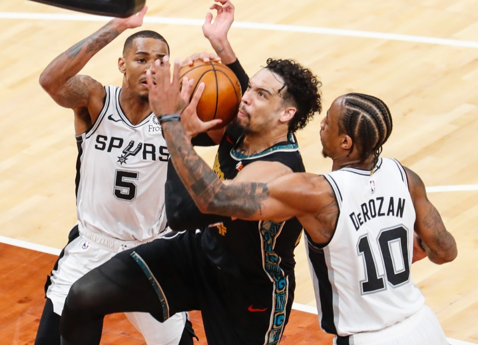 <strong>Grizzlies guard Dillon Brooks (middle) is fouled while driving the lane against San Antonio&rsquo;s Dejounte Murray (left) and DeMar DeRozan (right) on May 19, 2021, at FedExForum.</strong> (Mark Weber/The Daily Memphian)
