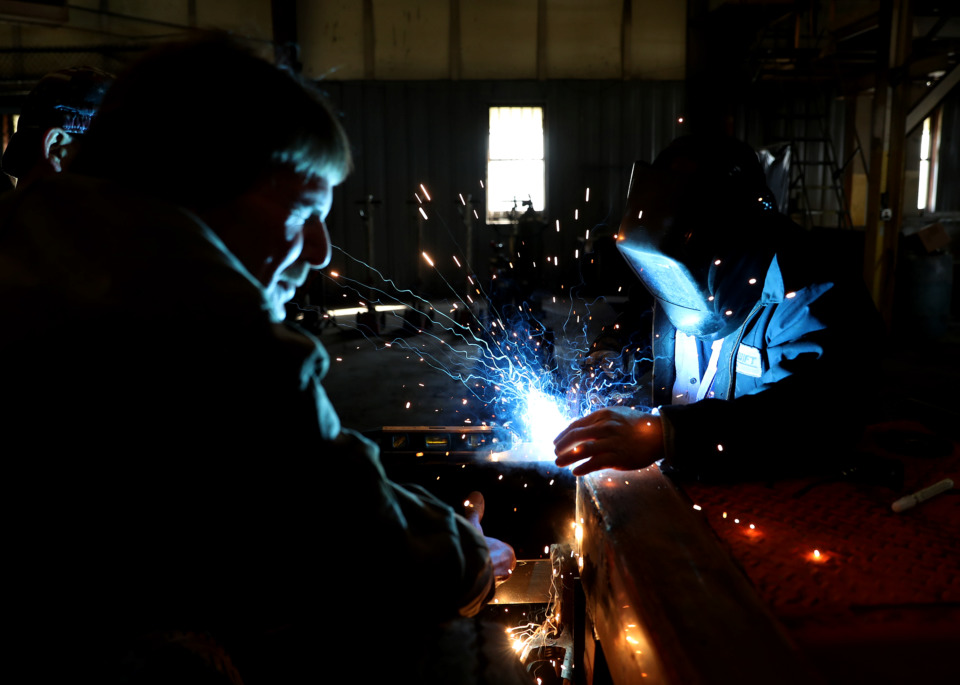 <strong>Lam Nguyen (right), a mechanic at IMC Chassis Services, welds a structural component for a tail light on a chassis in the restoration process. The company is capable of restoring between four and five chassis a day.</strong> (Houston Cofield/Daily Memphian)