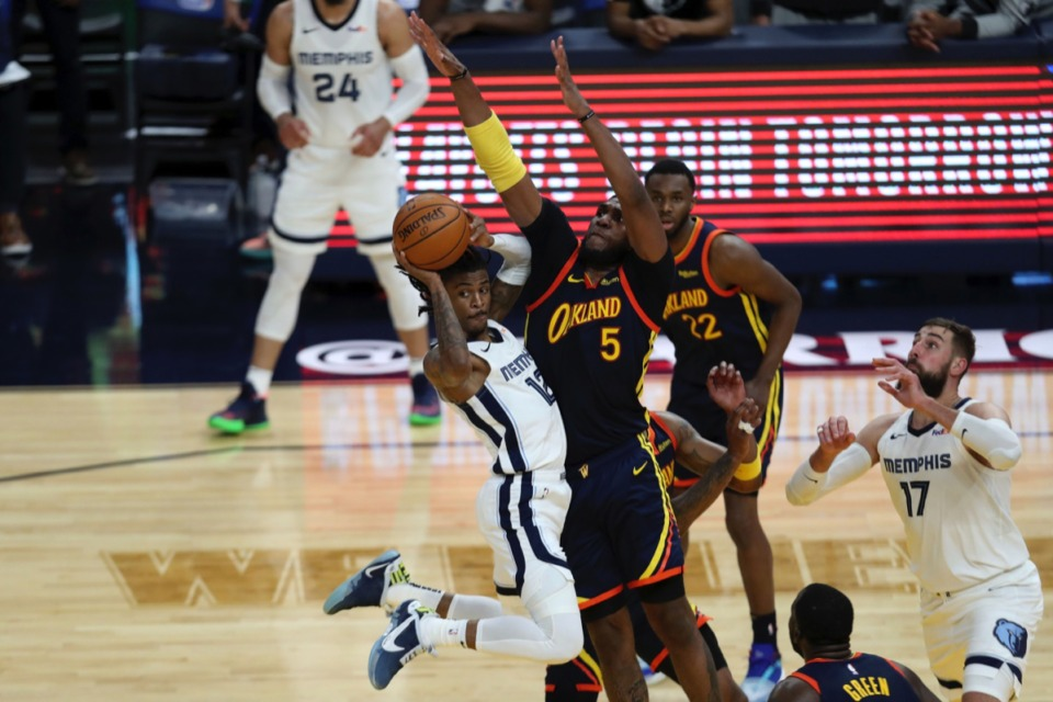 <strong>Memphis guard Ja Morant, left, drives against Golden State&rsquo;s Kevon Looney (5) during the play-in game in San Francisco Friday, May 21, 2021. Led by Morant, the Grizzlies beat the Warriors 117-112 in overtime to make the playoffs.</strong>&nbsp;(Jed Jacobsohn/AP)