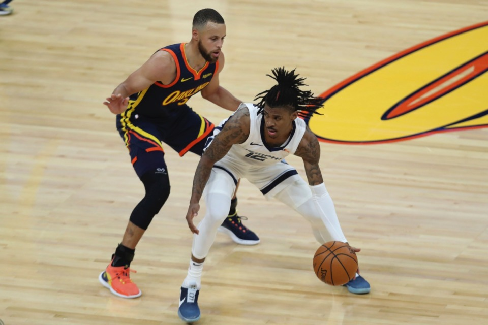 <strong>Grizzlies guard Ja Morant, right, drives against Golden State&rsquo;s Stephen Curry during the Western Conference play-in game in San Francisco Friday, May 21, 2021.</strong> (Jed Jacobsohn/AP)