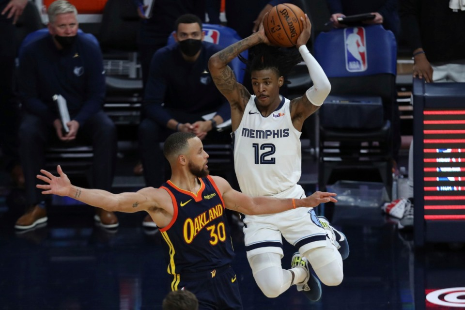 <strong>Grizzlies guard Ja Morant, right, passes against Golden State&rsquo;s Stephen Curry during the second half of the NBA basketball Western Conference play-in game in San Francisco Friday, May 21, 2021.</strong> (Jed Jacobsohn/AP)