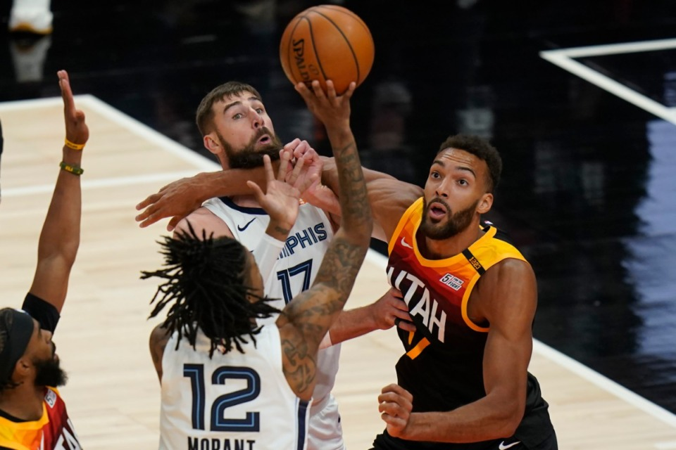 <strong>Grizzlies guard Ja Morant (12) shoots as Utah Jazz center Rudy Gobert (27) battles with Grizzlies center Jonas Valanciunas (17) during Game 2 of their NBA basketball first-round playoff series Wednesday, May 26, 2021, in Salt Lake City.</strong> (Rick Bowmer/AP)