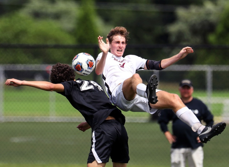 <strong>Bearden High School midfielder Dylan Kolnick (7) loses his footing while going up against Houston High School forward R.J. Jordan (24) in the Class AAA championship game in Murfreesoro, Tennessee, on May 28, 2021.</strong> (Patrick Lantrip/Daily Memphian)