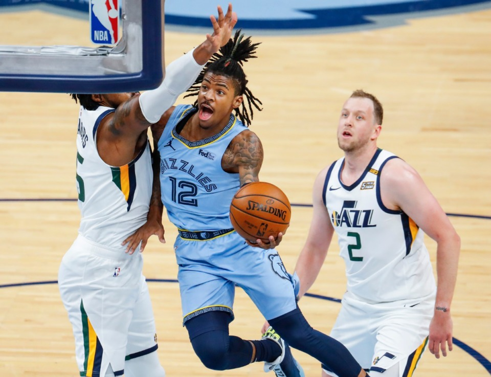 <strong>Memphis Grizzlies guard Ja Morant (middle) drives the lane against Utah Jazz defenders Derrick Favors (left) and Joe Ingles (right) during game three of the NBA Playoffs on Saturday, May 29, 2021.</strong> (Mark Weber/The Daily Memphian)