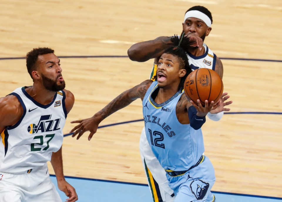 <strong>Memphis Grizzlies guard Ja Morant (middle) drives the lane against Utah Jazz defenders Rudy Gobert (left) and Royce O'Neale (back) during game three of the NBA Playoffs on Saturday, May 29, 2021.</strong> (Mark Weber/The Daily Memphian)