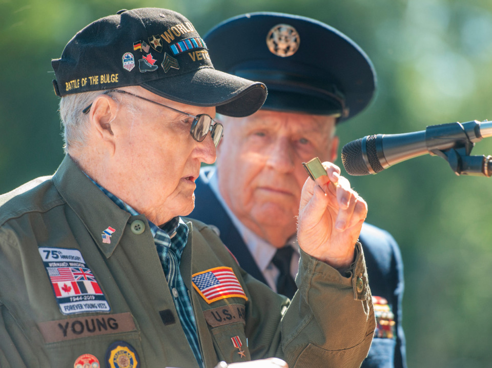 <strong>Jim Young, a World War II veteran and Battle of the Bulge survivor, shows his clicker used to communicate with other American soldiers during battle. Young is joined by Hugh Lamar at the Arlington Memorial Day service, Monday, May 31, 2021.</strong> (Greg Campbell/Special to Daily Memphian)