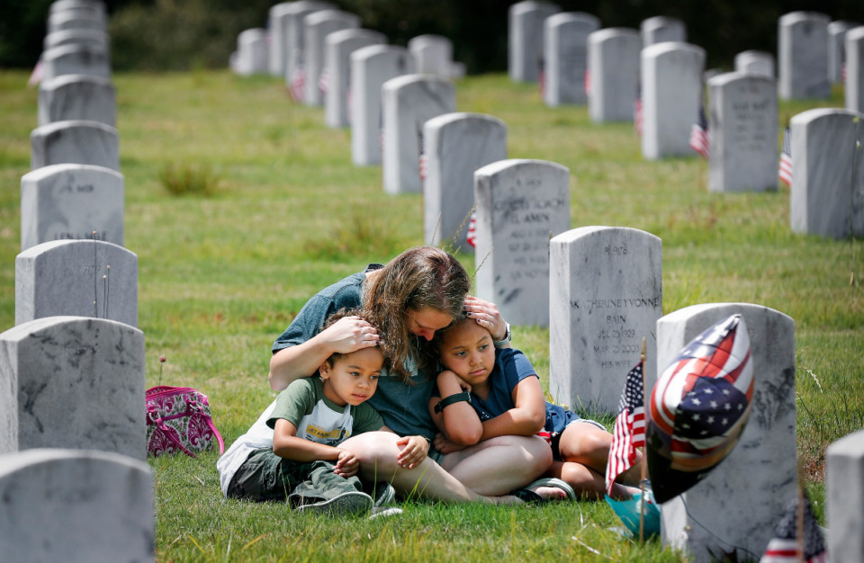 <strong>Rebecca Alston (middle) hugs her children Lincoln Alston, 6, (left) and Kennedy Alston, 8, while visiting her father&rsquo;s tombstone on Memorial Day at the West Tennessee Veterans Cemetery on Monday, May 31, 2021.</strong> (Mark Weber/The Daily Memphian)