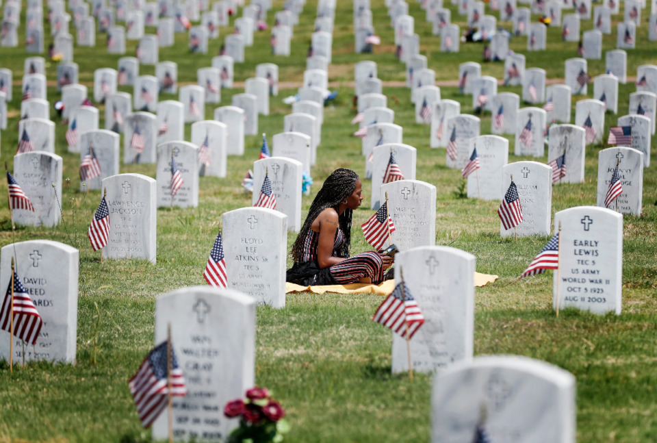 <strong>Nichole Jackson, reflects while sitting by the marker of her deceased mother on Memorial Day at the West Tennessee Veterans Cemetery on Monday, May 31, 2021.</strong> (Mark Weber/The Daily Memphian)