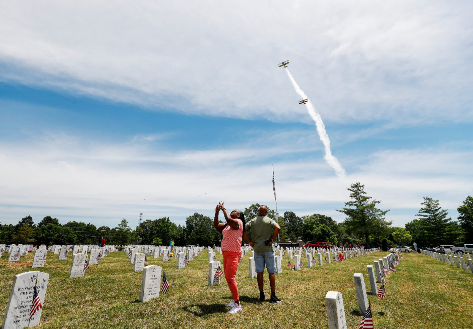 <strong>Family and friends visit loved ones as a Stearman planes blowing smoke pass overhead on Memorial Day at the West Tennessee Veterans Cemetery on Monday, May 31, 2021.</strong> (Mark Weber/The Daily Memphian)