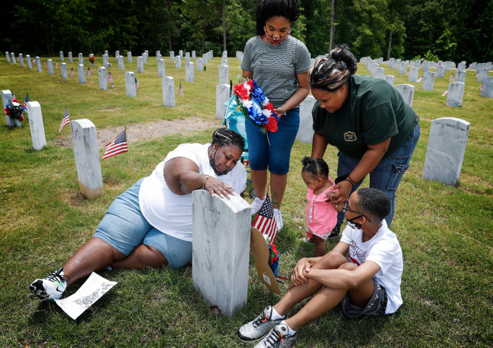 <strong>Tiera Harris (left) sheds tears while touching the her grandfather&rsquo;s tombstone with her children Akiriya Griffin, 11, (top left) Akaelah Griffin, 10 months, (middle) Damarien Griffin, 12, (right) and cousin Sabrina Shanklin (top right) on Memorial Day at the West Tennessee Veterans Cemetery on Monday, May 31, 2021.</strong> (Mark Weber/The Daily Memphian)