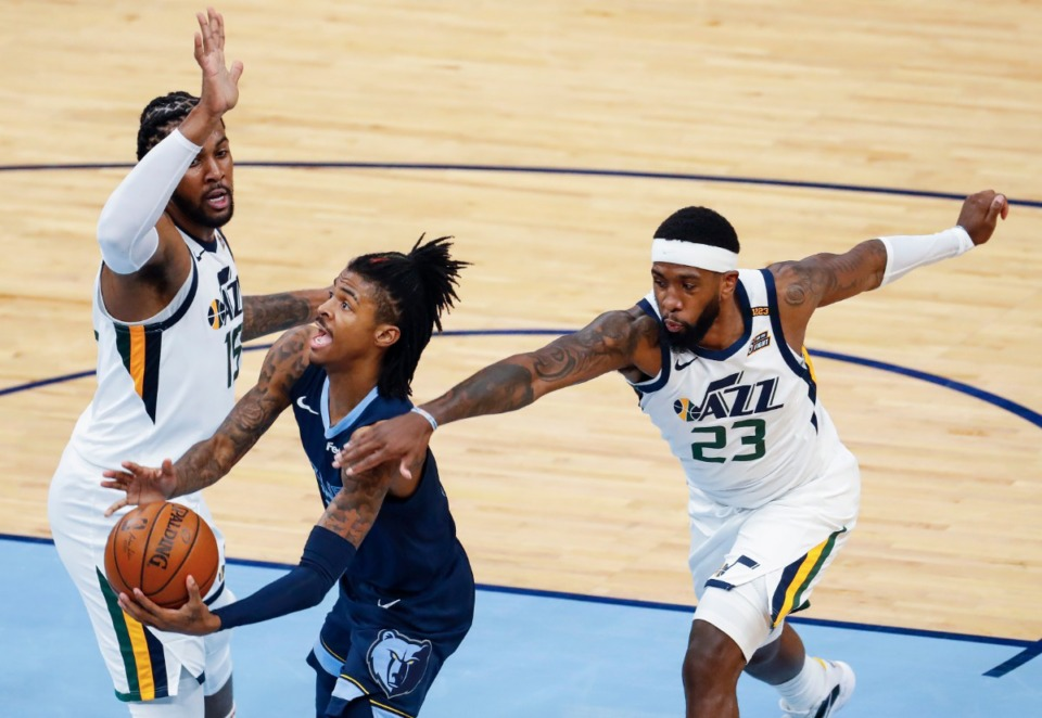 <strong>Memphis Grizzlies guard Ja Morant (middle) drives the lane against Utah Jazz defenders Derrick Favors (left) and Royce O'Neale (right) during action of game four of the NBA Playoffs on Monday, May 31, 2021.</strong> (Mark Weber/The Daily Memphian)