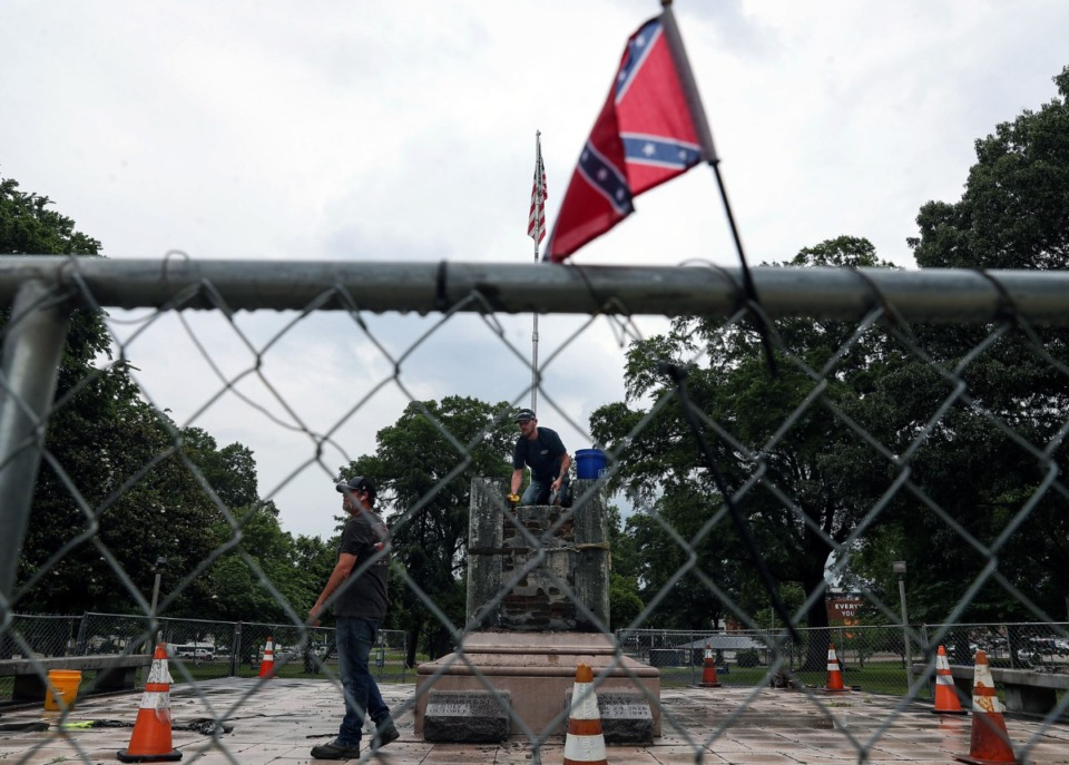 <strong>A small Confederate flag hangs on a fence as constructions crews hired by the family of Nathan Bedford Forrest work to dismantle his grave in Health Sciences Park June 1, 2021.</strong> (Patrick Lantrip/Daily Memphian)
