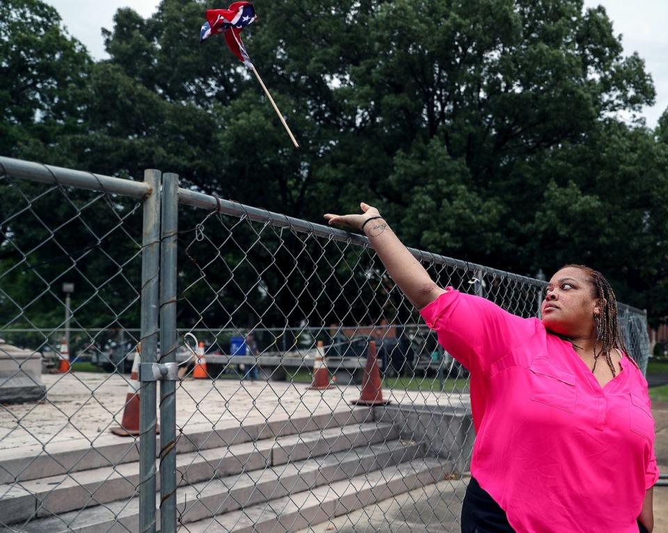 <strong>Shelby County Commissioner Tami Sawyer removes a Confederate flag hanging from the fence surrounding the grave of Nathan Bedford Forrest June 1, 2021.</strong> (Patrick Lantrip/Daily Memphian)