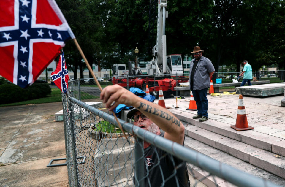 <strong>A man who identified himself as K-Rack Johnson replaces a confederate flag removed by Shelby County Commissioner Tami Sawyer after a June 1, 2021 press conference in Health Sciences Park.</strong> (Patrick Lantrip/Daily Memphian)