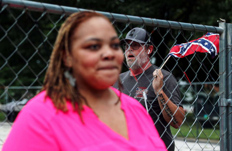 """A man who identified himself as K-Rack Johnson sings """"Dixie"""" while waving a confederate flag behind Shelby County Commissioner Tami Sawyer during a June 1, press conference in Health Sciences Park. (Patrick Lantrip/Daily Memphian)"""