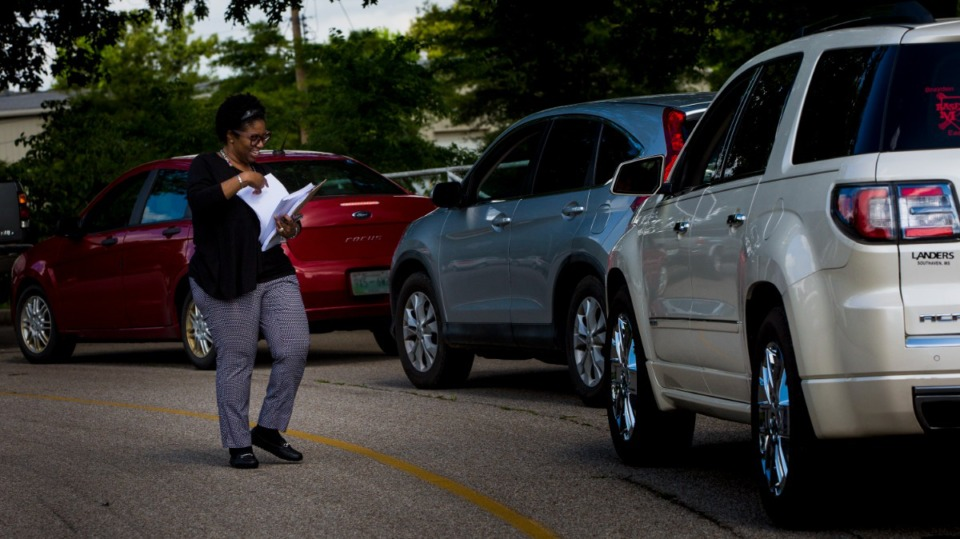 <strong>Arlington Community Schools associate Clara Earle disperses ordering forms to student families at Arlington High School to receive prepared food on June 3, 2021.</strong> (Ziggy Mack/Special to The Daily Memphian)