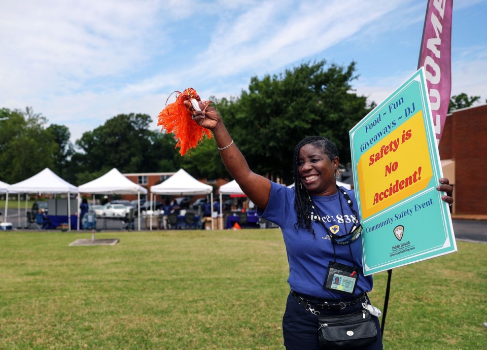 <strong>Sara Cotton with the Shelby County Health Department waves Saturday, June 5 to motorists driving down Watkins Street. She wanted to increase awareness of a public health fair at the Pursuit of God Transformation Center in Frayser.</strong> (Patrick Lantrip/Daily Memphian)