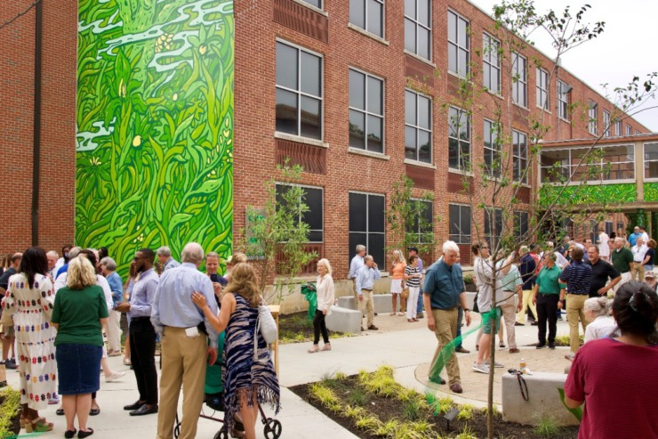About 100 people gathered for the ribbon cutting for White Station High's new courtyard. The transformed space includes the green mural projects led by artist and alum Rachel Briggs. (Tom Bailey/Daily Memphian)