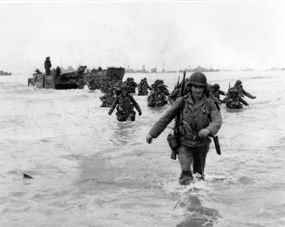 <strong>U.S. infantrymen wade through the surf as they land at Normandy in the days following the Allies' June 1944, D-Day invasion of occupied France. An allied ship loaded with supplies and reinforcements waits on the horizon.</strong> (AP Photo/Bert Brandt)