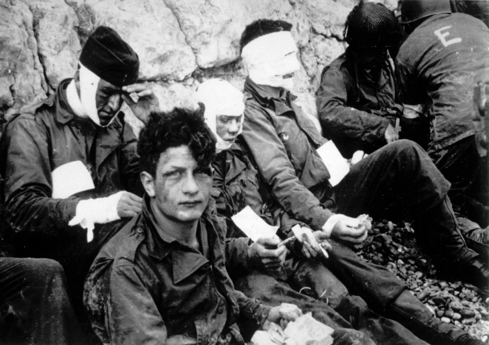 <strong>Men of the American assault troops of the 16th Infantry Regiment, injured while storming a coastal area code-named Omaha Beach during the Allied invasion of the Normandy, wait by the chalk cliffs at Collville-sur-Mer for evacuation to a field hospital for further treatment, June 6, 1944.</strong> (AP Photo)