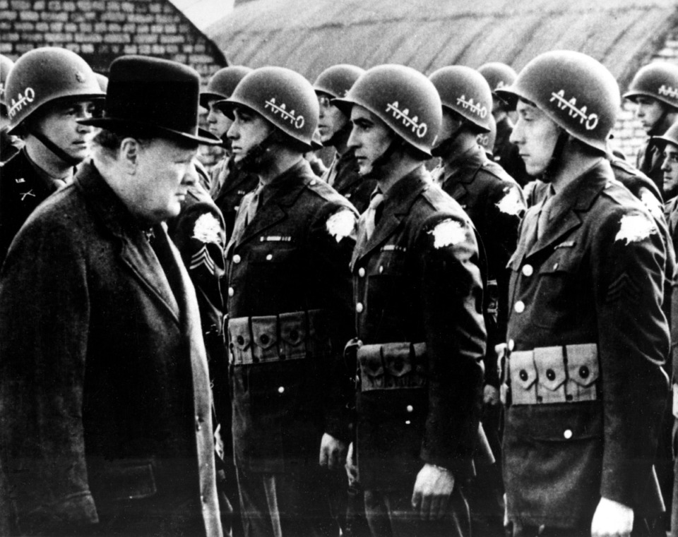 """<strong>British Prime Minister Winston Churchill, left, reviews American troops at a base in England on the eve of D-Day, June 1944, during World War II. The initials AAAO on the steel helmets with a line across the As stands for """"Anywhere, Anytime, Anyhow, Bar Nothing."""" The identification shoulder patches of the G.I.s are blotted out by the censor.</strong> (AP Photo)"""