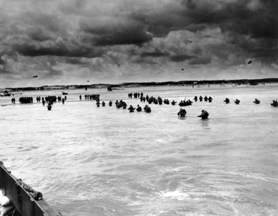 <strong>U.S. reinforcements wade through the surf as they land at Normandy in the days following the Allies', D-Day invasion of occupied France. The assault began the liberation of France and Europe from German occupation, leading to the end World War II.</strong> (U.S. Coast Guard via AP, File)