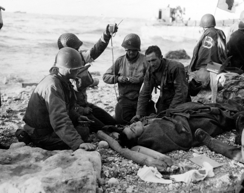 <strong>U.S. Army medical personnel administer a plasma transfusion to a wounded comrade, who survived when his landing craft went down off the coast of Normandy, France, in the early days of the Allied landing operations in June 1944.</strong> (AP Photo)