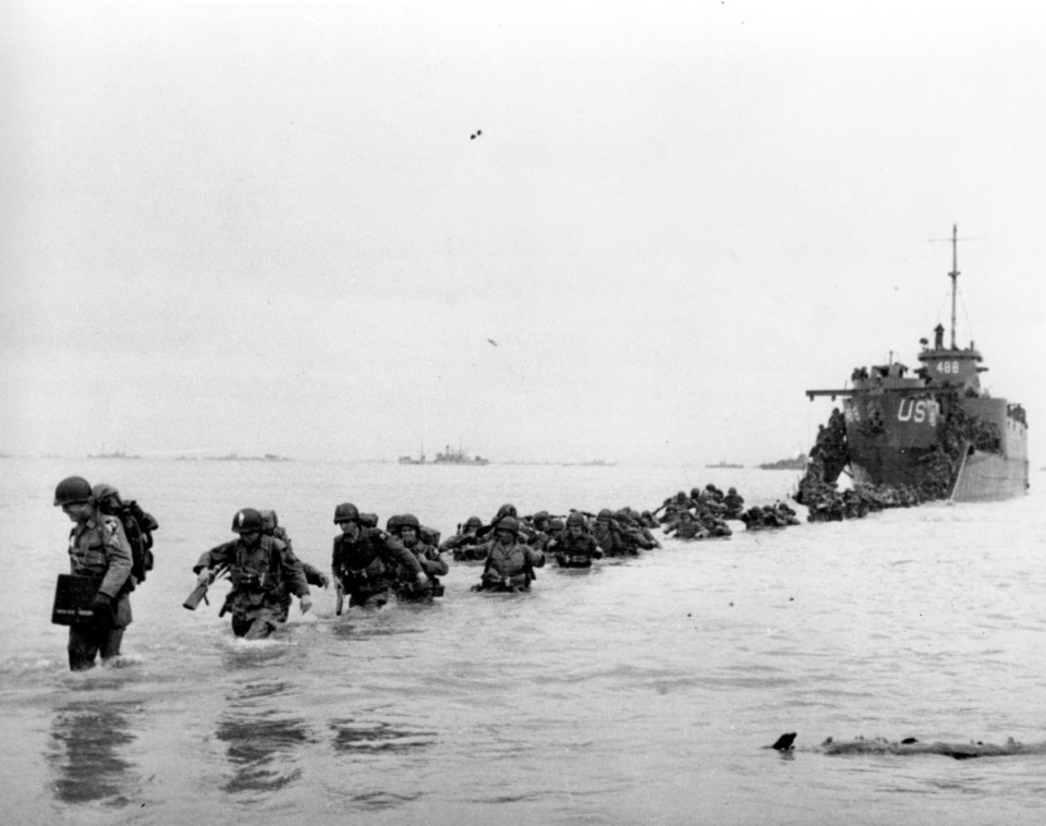 <strong>&nbsp;U.S. reinforcements wade through the surf from a landing craft in the days following D-Day and the Allied invasion of Nazi-occupied France at Normandy in June 1944 during World War II.</strong> (AP Photo/Bert Brandt, File)