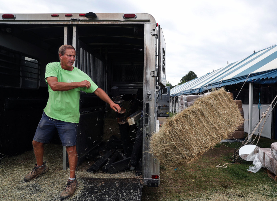 <strong>Beanie Cone unloads a bail of hay in preparation for the Germantown Horse Show June 5, 2021.</strong> (Patrick Lantrip/Daily Memphian)