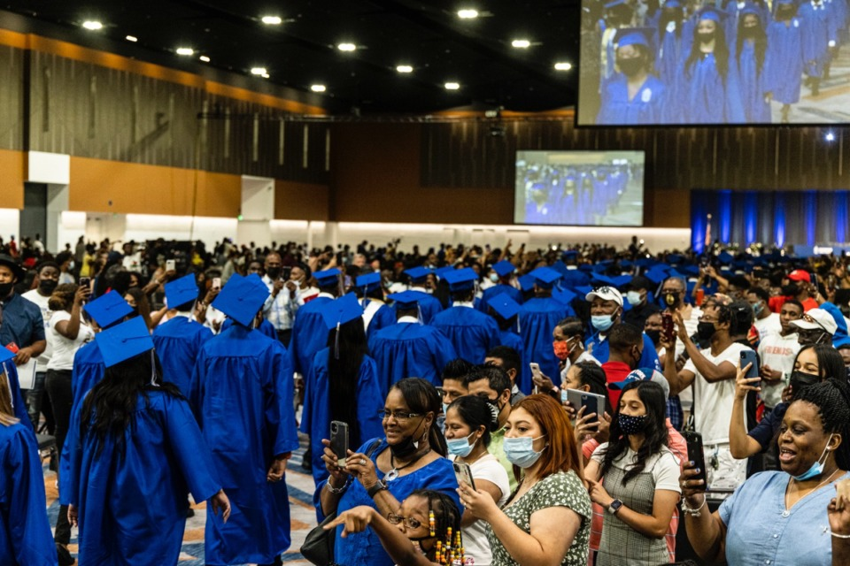 <strong>Family and friends take pictures as graduates walk in at the start of the Watkins Overton High School Commencement at the Renasant Convention Center on June 16.&nbsp;</strong>(Brad Vest/Special to The Daily Memphian