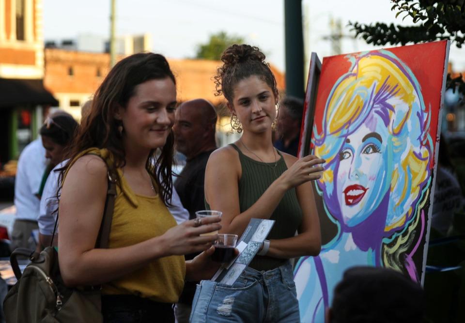 <strong>Olivia May (right) and Becka Matthews talk with artist Michael Maness at his South Main Trolley Night booth on June 25, 2021.</strong> (Patrick Lantrip/Daily Memphian)