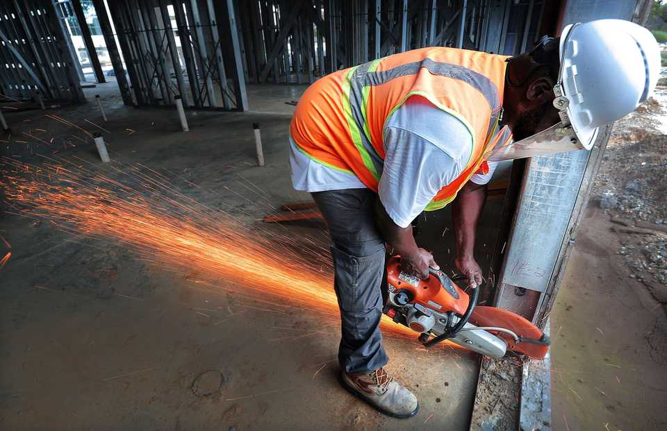 <strong>Contractor Javonte Johnson finishes cutting out door frames as construction continues on a Hilton Garden Inn, part of a dual-hotel complex at the $90 million TraVure mixed-use project in Germantown. </strong>(Jim Weber/Daily Memphian)