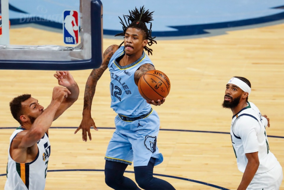 <strong>Memphis Grizzlies guard Ja Morant (middle) drives the lane against Utah Jazz defenders Rudy Gobert (left) and Mike Conley (right) during game three of the NBA Playoffs on Saturday, May 29, 2021.</strong> (Mark Weber/The Daily Memphian)