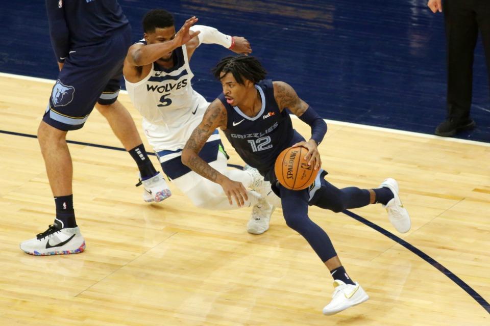 <strong>Memphis Grizzlies guard Ja Morant (12) drives on Minnesota Timberwolves guard Malik Beasley (5) during an NBA preseason basketball game, Saturday, Dec. 12, 2020 in Minneapolis.</strong> (AP Photo/Andy Clayton- King)