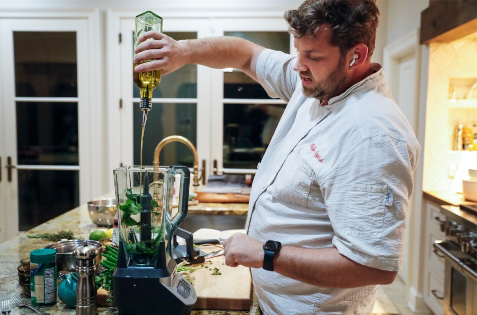 <strong>Chef Kelly English pours olive oil into a blender while making pesto sauce during a Zoom cooking class on Tuesday, Jan. 5, 2021.</strong> (Mark Weber/The Daily Memphian file)