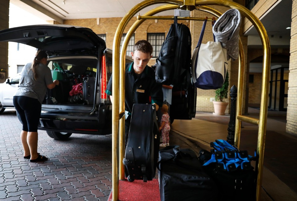 <strong>Bellhop Hunter Reid loads a luggage cart at The Peabody hotel on Monday, July 12. Post-pandemic demand from guests is climbing. But the hotel must limit the reservations it accepts and the number of events and banquets it hosts because of the labor shortage.</strong> (Mark Weber/Daily Memphian)