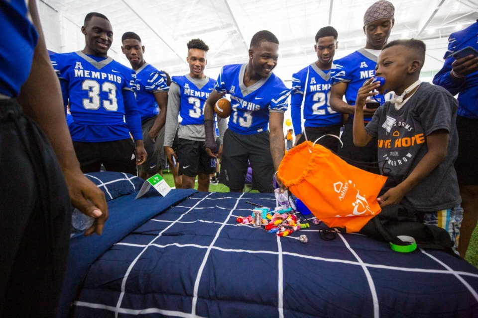 <strong>University of Memphis football team members, along with Hope to Dream affiliates, led a mini-camp for kids including Kingston Miller (right) Saturday at the University of Memphis South Campus, then helped the youngsters select beds and bedding to have at their homes.</strong> (Ziggy Mack/Special to Daily Memphian)