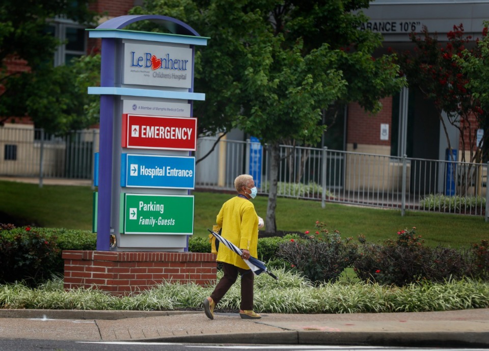 <strong>A Le Bonheur Children's Hospital staff member crosses Poplar Avenue, on Monday, July 19, 2021. The Medical District is announcing a $30M real estate investment fund to promote residential and mixed-use construction.</strong> (Mark Weber/The Daily Memphian)