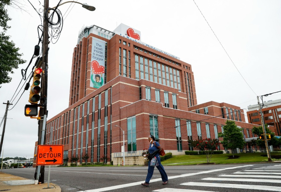 <strong>Le Bonheur Children's Hospital staff member crosses Poplar Ave., on Monday, July 19, 2021. The Medical District is announcing a $30M real estate investment fund to promote residential and mixed-use construction.</strong> (Mark Weber/The Daily Memphian)