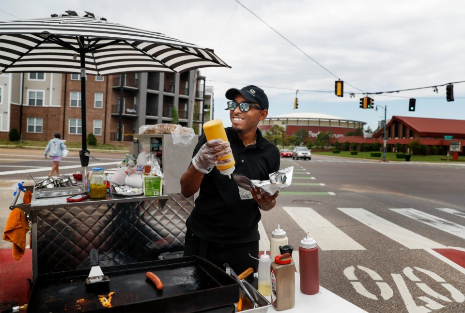 <strong>Aaron Branch, owner of A.D&rsquo;s food cart, smiles while serving customers on April 13, 2021. Branch will probably be smiling again Wednesday because it is National Hot Dog Day. </strong> (Mark Weber/The Daily Memphian file)
