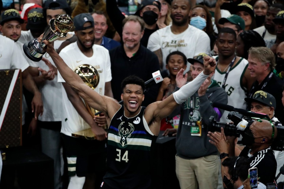 <strong>Milwaukee Bucks forward Giannis Antetokounmpo (34) celebrates with the MVP trophy, as teammates hold the championship trophy, after defeating the Phoenix Suns in Game 6 of basketball's NBA Finals Tuesday, July 20, 2021, in Milwaukee. The Bucks won 105-98.</strong> (AP Photo/Aaron Gash)
