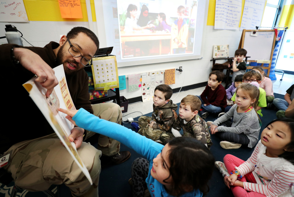 "<strong>Jonathan Pritchett (left), a school counselor at Farmington Elementary School in Germantown, helps one of his students, Caroline ""CC"" Lamia (center), 6, identify a character in a storybook. Pritchett reads, plays music and performs puppet shows to introduce good mental health practices as part of the curriculum in Germantown public schools.</strong> (Houston Cofield/Daily Memphian)"