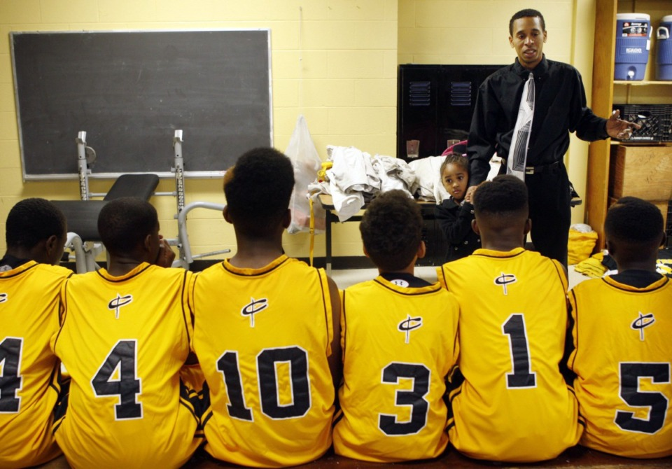 <strong>Nikcolauz Merriweather&rsquo;s late father Desmond Merriweather (right, in a Nov. 28, 2011 photo) talks to his team before a game in the Lester Middle School gym. His daughter Ziona Merriweather, 4, holds his hand.</strong> (Alan Spearman/AP file)