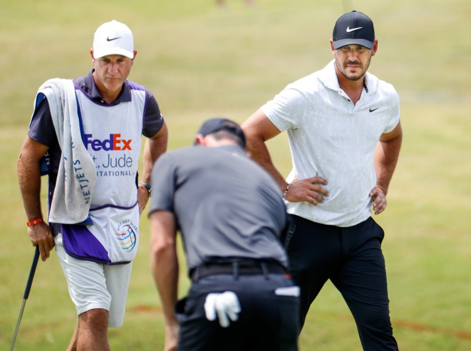 <strong>PGA golfer Brooks Koepka (right) and caddy watch Rory McIlroy (middle) putt on the 18th green&nbsp;during the first round of the WGC-FedEx St. Jude Invitational on Thursday, Aug. 5, 2021, at TPC Southwind.</strong> (Mark Weber/The Daily Memphian)