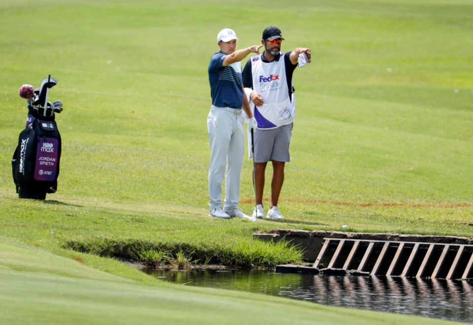 <strong>PGA golfer Jordan Spieth (left) and caddy line up hits shot after hitting into the water on the 18th hole&nbsp;during the first round of the WGC-FedEx St. Jude Invitational on Thursday, Aug. 5, 2021, at TPC Southwind.</strong> (Mark Weber/The Daily Memphian)