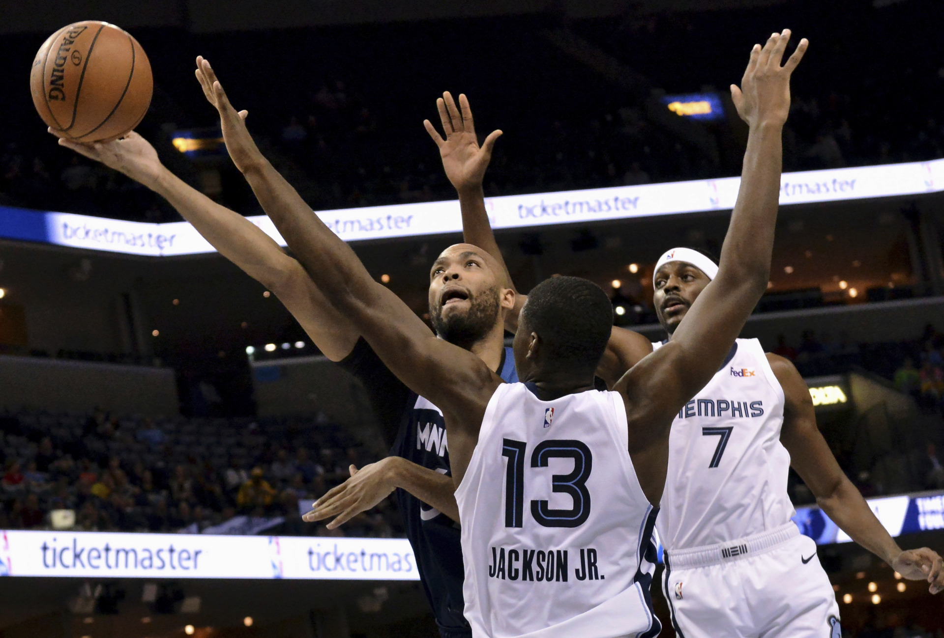 <span><strong>Minnesota Timberwolves forward Taj Gibson shoots against Memphis Grizzlies forwards Jaren Jackson Jr. (13) and Justin Holiday (7) Tuesday, Feb. 5, 2019, in Memphis. Holiday's last-second free throws helped the Grizzlies eke out a win, 108-106.</strong>&nbsp;(AP Photo/Brandon Dill)</span>