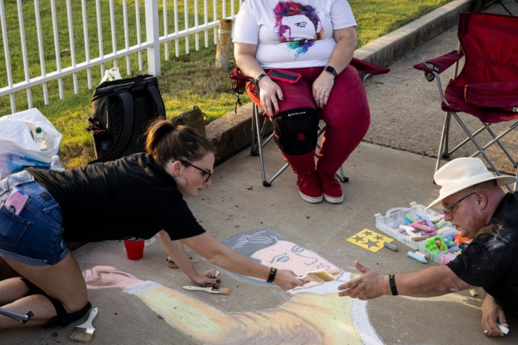 <strong>Haley Damron (left) passes a brush to her father, Greg Damron, while creating sidewalk art along Elvis Presley Boulevard during the Elvis Week Candlelight Vigil, Sunday, Aug. 15, 2021.</strong> (Brad Vest/Special to The Daily Memphian)