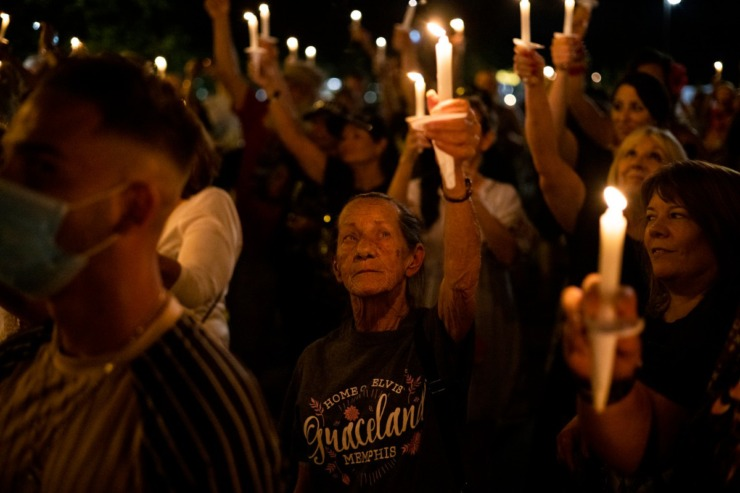 <strong>Fans hold their candles high Sunday, Aug. 15, 2021 as they stand along Elvis Presley Boulevard during the Elvis Week 2021 Candlelight Vigil. The vigil marks the anniversary of the singer&rsquo;s death on Aug. 16, 1977.</strong> (Brad Vest/Special to The Daily Memphian)