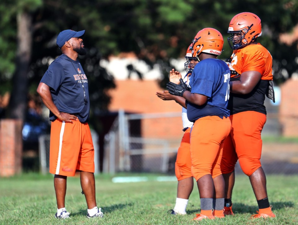 <strong>Ridgeway football coach Duron Sutton (left) talks with a few of his players at a July 27, 2021, practice.</strong> (Patrick Lantrip/Daily Memphian file)