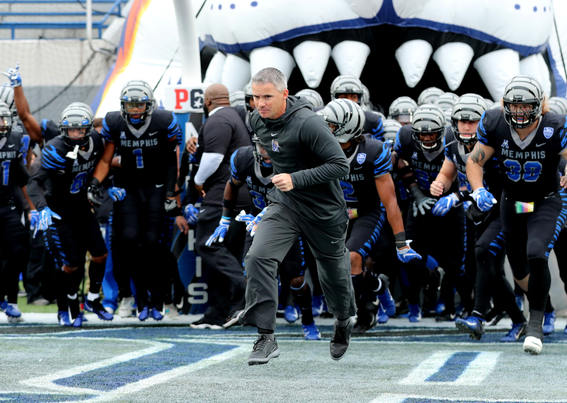 <strong>Memphis Tigers head coach Mike Norvell sprints onto the field Nov. 23, 2018, for the last home game of the year against the Houston Cougars. Norvell added seven more players on national signing day Wednesday.</strong> (Houston Cofield/Daily Memphian)